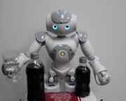 Nao robot places an effervescent antacid in a glass of water.